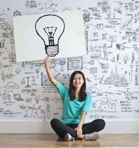 A girl holding a sign with a light bulb and shows that she has an idea with a white board behind her with many drawings