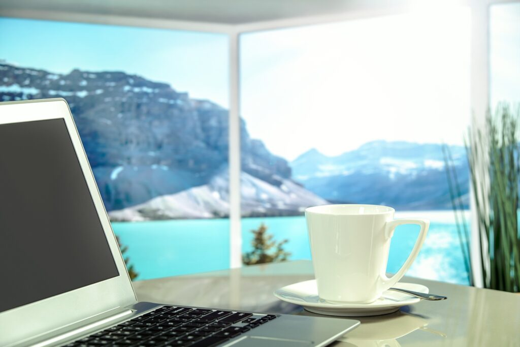 Coffee and laptop on a work desk with a view through the window of sea and nature