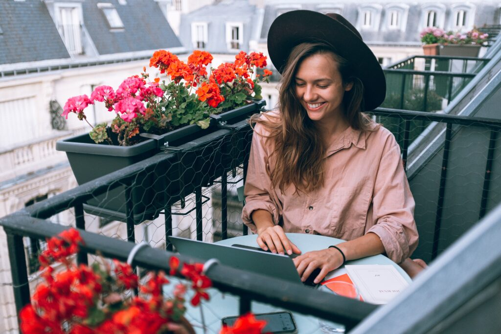 Woman working on a terrace from her laptop surrounded by flowers